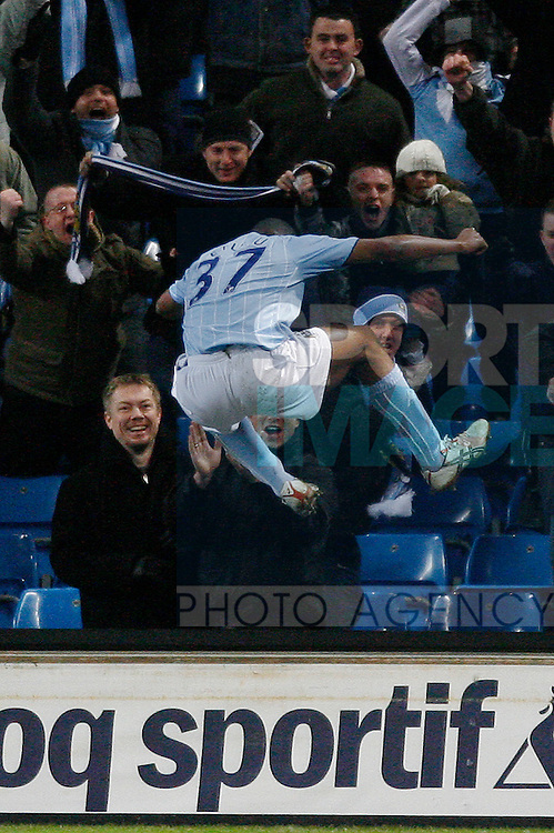 Manchester City's Kelvin Etuhu leaps over the boards to celebrate his goal with the fans