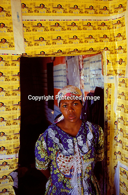 "SIDEPRE20015.Social Issues. Depression. Depressed woman standing in a doorway, '99. Shack with ""Oom Tas"" bottle labels as wallpaper..©Per-Anders Pettersson/iAfrika Photos."