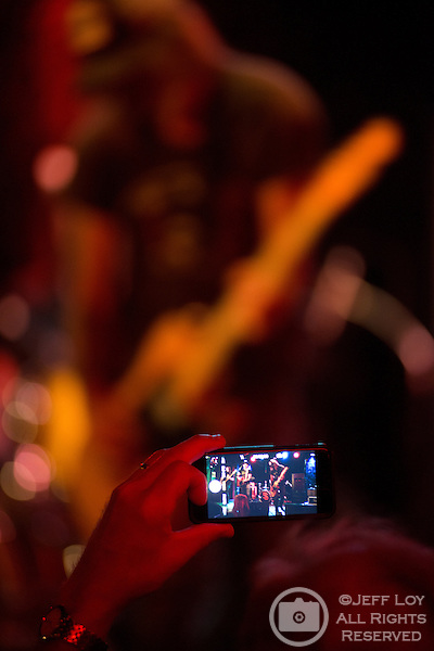 A fan takes a photo as the Supersuckers perform at Dan's Silver Leaf in Denton, Texas.