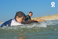 Two boys (10-11, 12-13) surfing in ocean  (Licence this image exclusively with Getty: http://www.gettyimages.com/detail/200553555-001 )