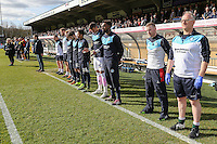 The two benches and fans observe a minute's silence in memory of the victims of the Brussels attack earlier in the week ahead of the Sky Bet League 2 match between Wycombe Wanderers and Mansfield Town at Adams Park, High Wycombe, England on 25 March 2016. Photo by David Horn.