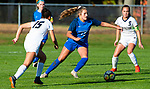 BURLINGTON ,  CT-101519JS14-  Lewis Mills' Victoria Fleming (12) pushes the ball up field between Newington's Olivia Mullings (15) and Cassidy Gilchrest (9) during their game Tuesday at Nassahegan Field in Burlington. <br /> Jim Shannon Republican-American