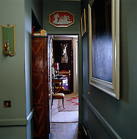 The corridor has been painted a cool Georgian green and  displays a collection of paintings and works of art