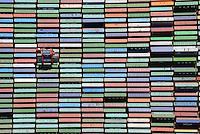 Container und Carrier am Burchardkaii: EUROPA, DEUTSCHLAND, HAMBURG, (EUROPE, GERMANY), 29.06.2014 Der HHLA Container Terminal Burchardkai ist die groesste und aelteste Anlage f&uuml;r den Containerumschlag im Hamburger Hafen. Hier, wo 1968 die ersten Stahlboxen abgefertigt wurden, wird heute etwa jeder dritte Container des Hamburger Hafens umgeschlagen. 25 Containerbruecken arbeiten an den Tausenden Schiffen, die hier jaehrlich festmachen, und taeglich werden mehrere Hundert Eisenbahnwaggons be- und entladen. Mit dem laufenden Aus- und Modernisierungsprogramm wird die Kapazit&auml;t des Terminals in den kommenden Jahren schrittweise ausgebaut. <br /> Der wichtigste und bekannteste Containertyp ist der 40 feet Container fuer die Handelsschifffahrt mit den Ma&szlig;en 12,192 &times; 2,438 &times; 2,591 m. Von diesem Containertyp nach ISO 668 (freight container) sind ueber Millionen im Verkehr.<br /> Der Fracht- oder Schiffscontainer wurde im Jahr 1956 von dem Reeder Malcolm McLean an der US-Ostkueste fuer den Gueterverkehr eingefuehrt.  Die Frachtcontainer wurden zur Basis der Globalisierung der Wirtschaft; mit ihnen wird u. a. der Grossteil des Warenhandels mit Fertigprodukten abgewickelt. <br /> 20-Fu&szlig;-Container &ndash; die sogenannten TEU (Twenty-foot Equivalent Unit) &ndash; und 40-Fu&szlig;-Container (FEU = forty foot equivalent unit):<br /> Die 20&rsquo;-Standardcontainer messen (au&szlig;en) 6,058 &times; 2,438 &times; 2,591 Meter. Ein Container Carrier bring einen Container zu einem fest bestimmten Platz.