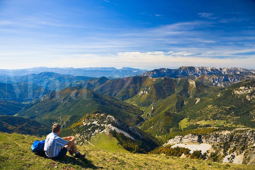 Walker relaxes on the summit of Mt. Jocou and enjoys the view towards the Vercors Plateau. Diois. Drome. France.
