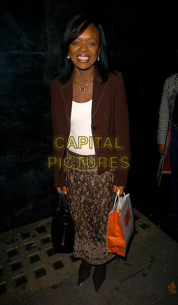 RONCAI PHILLIPS.The Indian Infusion VIP Launch Party, Pangaea nightclub, London, UK..October 12th, 2006.Ref: CAN.full length brown skirt pattern jacket goody bag.www.capitalpictures.com.sales@capitalpictures.com.©Can Nguyen/Capital PicturesP