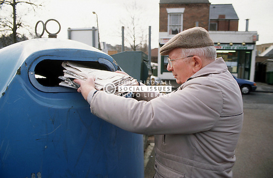 Elderly man recycling newspapers,