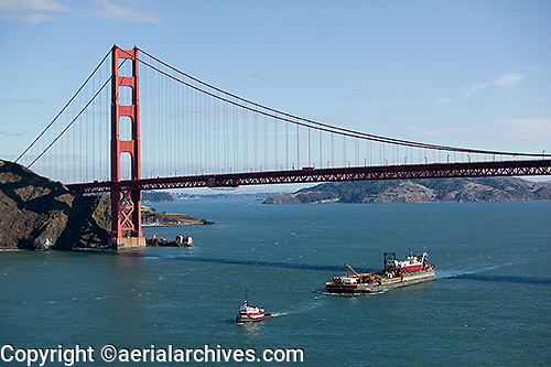 aerial photograph tug boat pulling loaded barge under the Golden Gate bridge, San Francisco, California