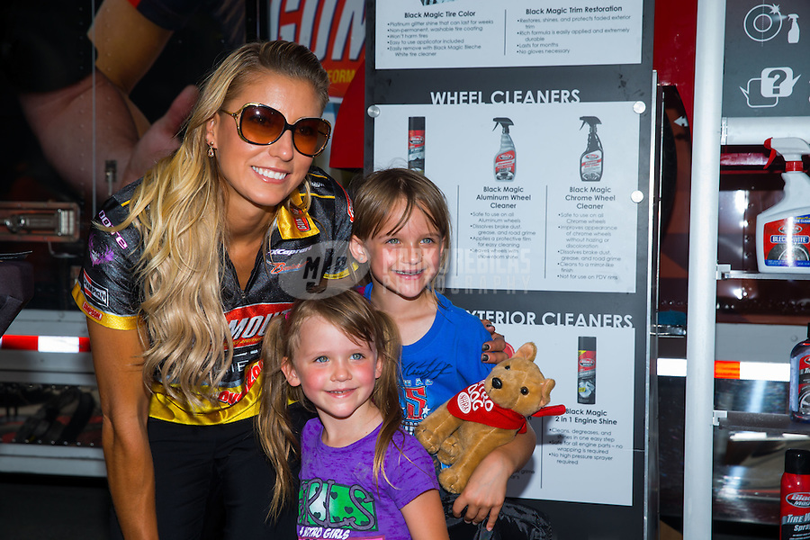 Jun 19, 2015; Bristol, TN, USA; NHRA top fuel driver Leah Pritchett poses with a couple of young fans during qualifying for the Thunder Valley Nationals at Bristol Dragway. Mandatory Credit: Mark J. Rebilas-