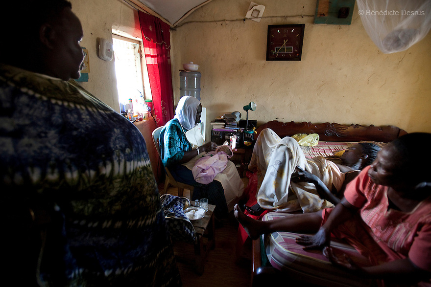 July 18, 2011 - Juba, Republic of South Sudan - Lushi Rashid (C), a 29 year old muslim South Sudanese woman, a few minuts after giving birth to her fifth child at her family home with the help of her mother Marcelina Dudu (L), her neighbor (R) and Regabia Ahmad (L), a qualified birth attendant, in Juba, the capital city of South Sudan. Regabia has been delivering babies in South Sudan for over twenty years. she was trained by the health ministry and works at a local primary health clinic. With fewer than 100 trained midwives for a population of over eight million, South Sudan has the highest maternal mortality rate in the world.  One in seven South Sudanese women is likely to die because of complications from delivery. Just 10 per cent of South Sudanese women have access to medical professionals during childbirth. Photo credit: Benedicte Desrus