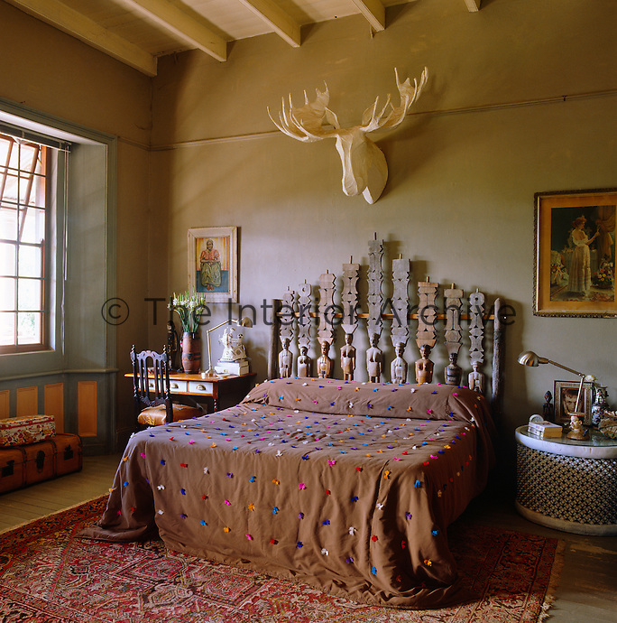 This bedhead is made of totems from Madagascar while the bed has a cover of multicoloured tufts and a Swedish elk trophy is mounted on the wall above it