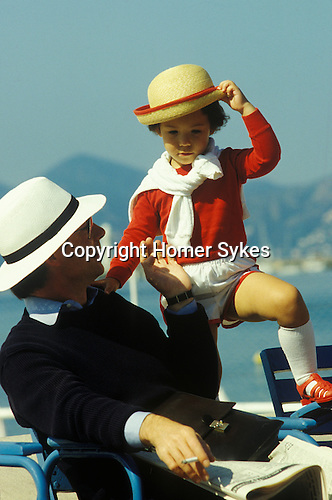 Smartyly dressed in similar style father and son Cannes 1980s. France.