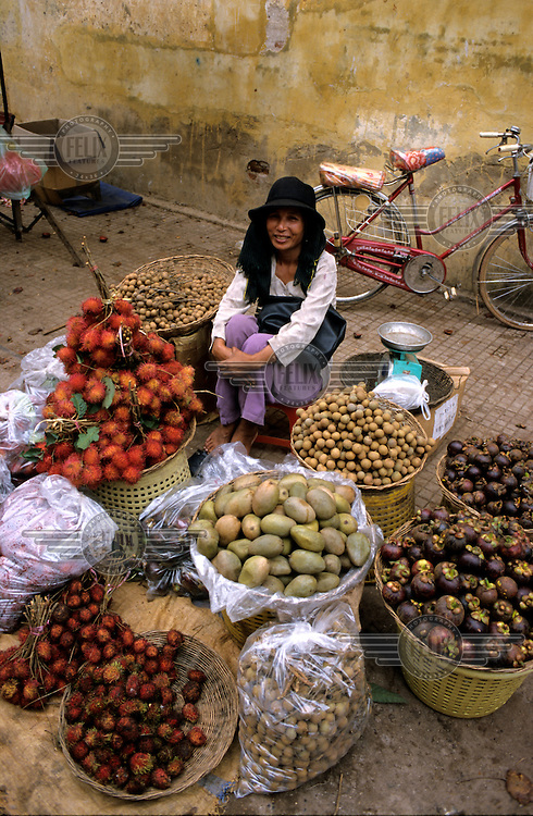 A woman selling fruit and vegetables at a downtown market.