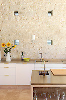 An unusual feature of teh kitchen are the small square windows, which are at eye-level and frame views of the fields of sunflowers and millet