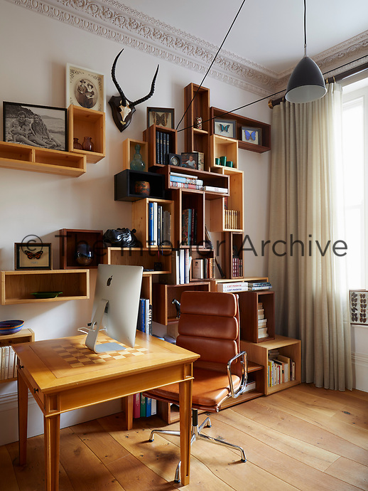 In the study, the use of light wood for the flooring, desk and shelving cubes gives the room a warm feel. A brown leather office chair adds a retro touch.
