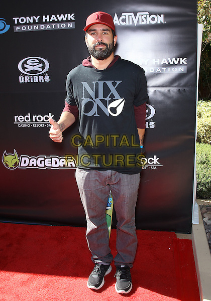 Mike Escamila.Tony Hawk's 3rd Annual Stand Up For Skateparks fundraiser at Red Rock Station Hotel and Casino, Las Vegas, Nevada, USA.  .November 5th, 2011.full length jeans denim black t-shirt red baseball cap hat beard facial hair.CAP/ADM/MJT.© MJT/AdMedia/Capital Pictures.