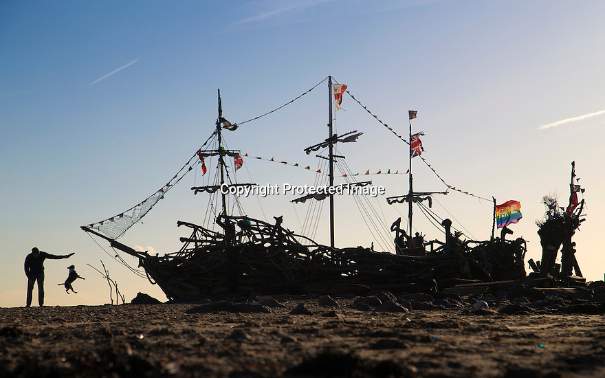 28/11/16<br /> <br /> As the cold front sweeps in with blue skies and freezing temperatures, Tony Tregenza  throws a frisbee for his pug Fergus by the Black Pearl pirate ship, made completely out of driftwood, on New Brighton beach near Liverpool. The boat was built in 2013 by local artist Frank Lund and his friend Major Mace using materials found on their beach walks. The work of art has survived numerous storms and being set alight by vandals and is now a popular spot for tourists and locals alike. There was even a pirate wedding held on its deck last year.<br /> <br /> All Rights Reserved F Stop Press Ltd. (0)1773 550665   www.fstoppress.com