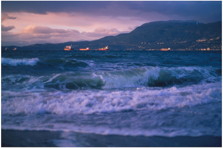 Waves crashing onto Kitsilano Beach, with tankers anchored in English Bay waiting to unload cargo at the Port of Vancouver.