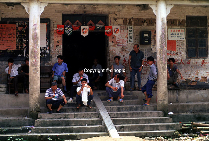 A group of single men gather at the door of their village council. This shows the effect of the one-child policy result in China.<br /> &copy;sinopix