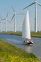 Holland Vestas Windmill at canal with sailing boat / Holland Vestas Windkraftanlagen an einem Kanal mit Segelboot