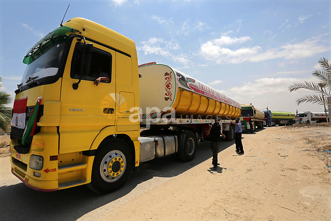 Palestinian security forces stand guard as Egyptian trucks carrying fuel enter the southern Gaza Strip from Egypt through the Rafah border crossing on June 21, 2017. Egypt began to deliver a million litres of fuel to Gaza, a Palestinian official said, in an attempt to ease the Palestinian enclave's desperate electricity crisis. The fuel, trucked in through the Rafah border between Egypt and Gaza, will be routed to the territory's only power station -- closed since April due to fuel shortages. Photo by Ashraf Amra