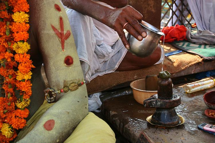 29.10.2006 Varanasi(Uttar Pradesh)<br /> <br /> Brahmine  blessing majiruana in the shiva lingam with water before taking it in the mouth.<br /> <br /> Brahmine bénissant de la majiruana sur le shiva lingam avec de l'eau avant de le prendre dans la bouche.