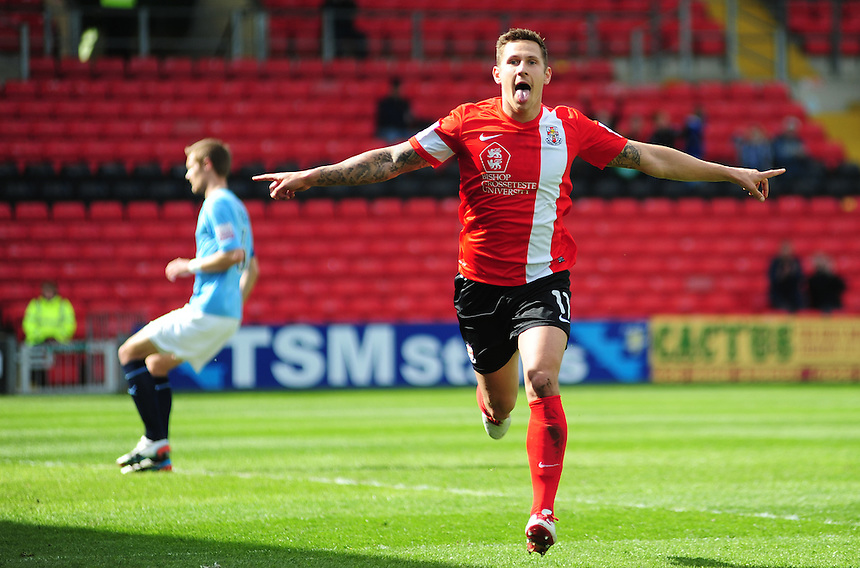 Lincoln City's Ben Tomlinson celebrates scoring the opening goal <br /> <br /> Photo by Chris Vaughan/CameraSport<br /> <br /> Football - The Skrill Premier - Lincoln City v Cambridge United - Friday 18th April 2014 - Gelder Group Sincil Bank Stadium - Lincoln<br /> <br /> &copy; CameraSport - 43 Linden Ave. Countesthorpe. Leicester. England. LE8 5PG - Tel: +44 (0) 116 277 4147 - admin@camerasport.com - www.camerasport.com