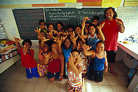 Group of Polynesian school kids with their teacher, in classroom in front of blackboard, Fatu Hiva, Marquesas, French Polynesia