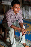 "Jewel Mahammud Kawsan (17) sits for a portrait in the meeting hut of a Children's Group in Bhashantek Basti (Slum) in Zon H, Dhaka, Bangladesh on 23rd September 2011. When asked if an abused wife could return to her family, Jewel says, ""Society doesn't take it well. It is not accepted if she leaves the husband's house. Even (her own parents) will tell her to be accommodative even if her husband beats her, because after marriage, that is now her real address."" Jewel also tells a true story of a girl who used to be a member of the children's group. When she turned 14/15, her parents wanted to marry her off. The children's group went to village elders to counsel the family and the marriage was stopped. The children felt proud but sadly, after 2 months, she was quietly married off. Now, at 18, she is a mother of a girl child and is not happy in the marriage. Her husband is also a young boy but is violent in nature and beats her. She is tied to motherhood and house chores and not allowed to join the other children. The families are also fighting because of dowry related issues."" The Bhashantek Basti Childrens Group is run by children for children with the facilitation of PLAN Bangladesh and other partner NGOs. Slum children from ages 8 to 17 run the group within their own communities to protect vulnerable children from child related issues such as child marriage. Photo by Suzanne Lee for The Guardian"