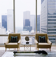 A pair of 1950s armchairs are placed against the floor to ceiling windows of the living room with magnificent views over Manhattan
