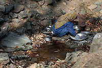 A girl washing pots and pans in in a small pool of water. A tiny brook is the only source of water near her house. Kashmir, India. © Fredrik Naumann/Felix Features