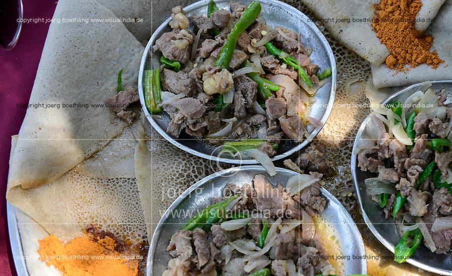 ETHIOPIA, national meal Injera with meat , onions, paprika and chillies powder, injera is a sour dough flat bread made from tef flour, ithas a spongy texture / AETHIOPIEN, Gambela, Injera Fladenbrot aus Tef mit Ziegenfleisch Zwiebeln und Chillies, der Teig des Fladenbrot wird aus Teff Zwerghirse sauer gegoren zubereitet