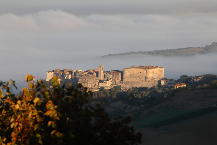 A view of the historical center of Alviano in the early morning, at the sunrise, where the old building are just enlightened, against the background of the fog that covers the Tiber valley. Digitally Improved Photo.