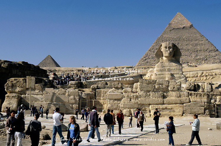 Tourists visiting the Great Sphinx of Giza, with The Khephren and The Mycerinus pyramids in the background, Giza, Cairo, Egypt.