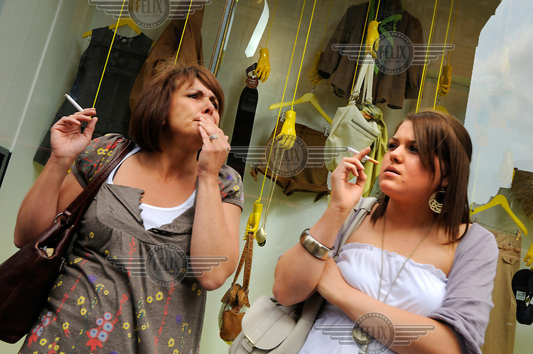 Women smoking on the street in front of a fashion store on Oxford Street, London.