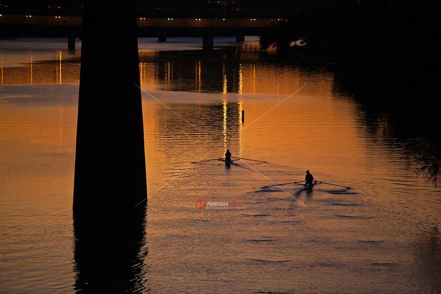 Rowers practice during vibrant sunrise on Lake Austin