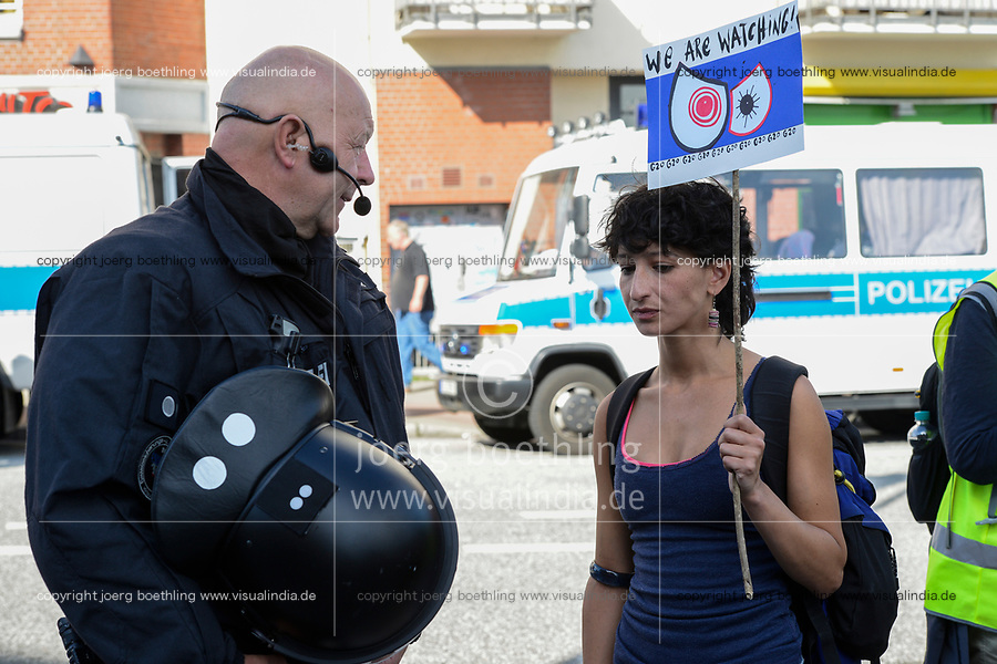 "GERMANY, Hamburg, protest rally ""WELCOME TO HELL"" against G-20 summit in july 2017, policeman and woman with banner We watch you / DEUTSCHLAND, Hamburg, Fischmarkt, Protest Demo WELCOME TO HELL gegen G20 Gipfel in Hamburg, Polizist und Demonstrantin"