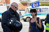 "GERMANY, Hamburg, protest rally ""WELCOME TO HELL"" against G-20 summit in july 2017, policeman and woman with banner We watch you / DEUTSCHLAND, Hamburg, Fischmarkt, Protest Demo WELCOME TO HELL gegen G20 Gipfel in Hamburg, Polizist und Demonstrantin"