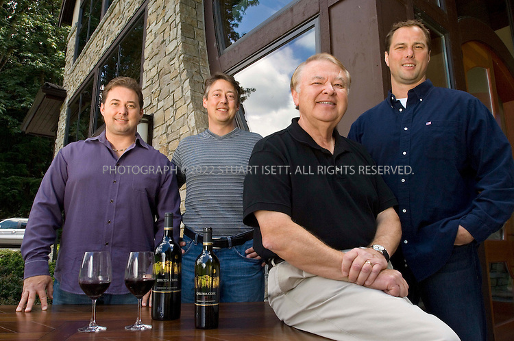 7/24/2007--Snohomish, WA, United States..From left to right:  Paul Golitzin,  John Ware, Alex Golitzin and Marv Crum posing outside the Quilceda Creek Winery, 45 minutes drive north of Seattle, with bottles of their 2004 cabernet sauvignon on a table. One of the earliest producers of cabernet sauvignon there and now one of the best in the country. It's a family operation, run mostly by Alex Golitzin and his son, Paul. Also involved are John Ware and Marv Crum (they are both related to the Golitzin's)...Photograph ©2007 Stuart Isett.All rights reserved