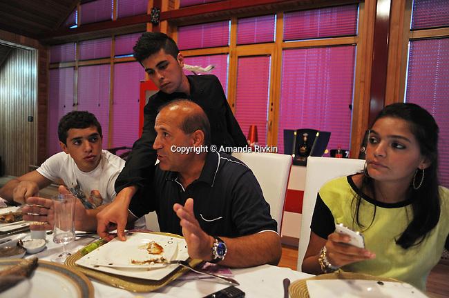 Ibrahim Ibrahimov (center) sits at the dinner table and eats steak with his son Huseyn Ibrahimov, 18, and daughter Ilkana Ibrahimova, 22, in his home between Sangachal and Sahil, Azerbaijan on August 16, 2012.