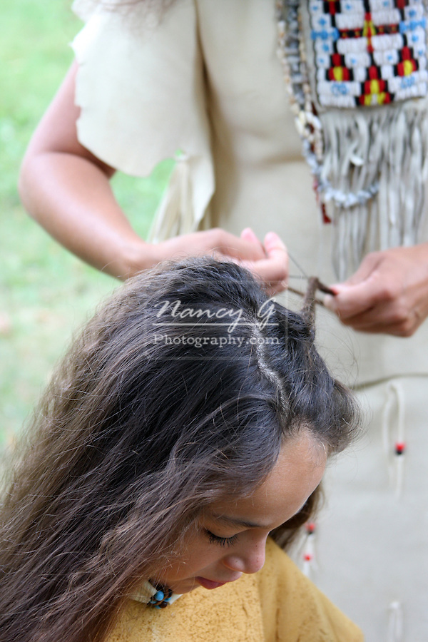 A Native American Indian woman braiding the hair of a young boy