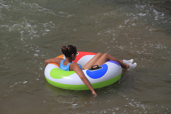 Woman floating in inner tube at Boulder Creek, Boulder, Colorado .  John offers private photo tours in Denver, Boulder and throughout Colorado. Year-round.
