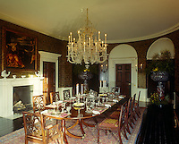 A formal oval-shaped dining room graced with a crystal chandelier has a table laid for a candlelit dinner
