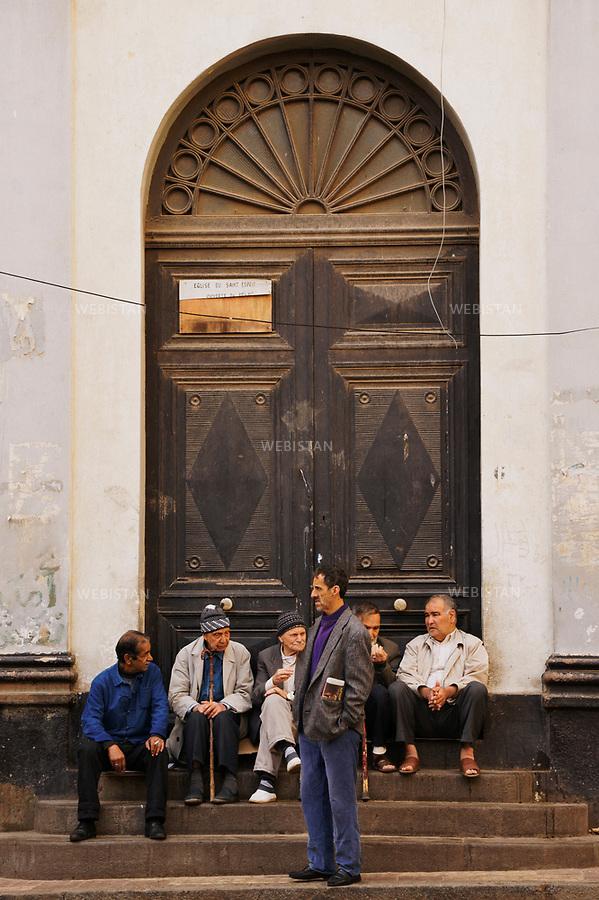 Algerie. Oran. Place du Maghreb  ou ancienne place de la Bastille. 08 avril 2011. Des hommes discutent a  l'entree de l'eglise catholique &laquo; Saint-Esprit &raquo;.<br /> <br /> <br /> Algeria, Oran. Maghreb Place or the ancient Bastille place. April 8th 2011<br /> Some men are having a discussion at the entrance of a Catholic church &quot;Holy Spirit&quot;.