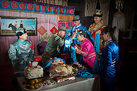A Mongolian bride (2nd-R) and parents perform a traditional rite during a wedding ceremony in Damao Banner, Inner Mongolia, China, October 2014.