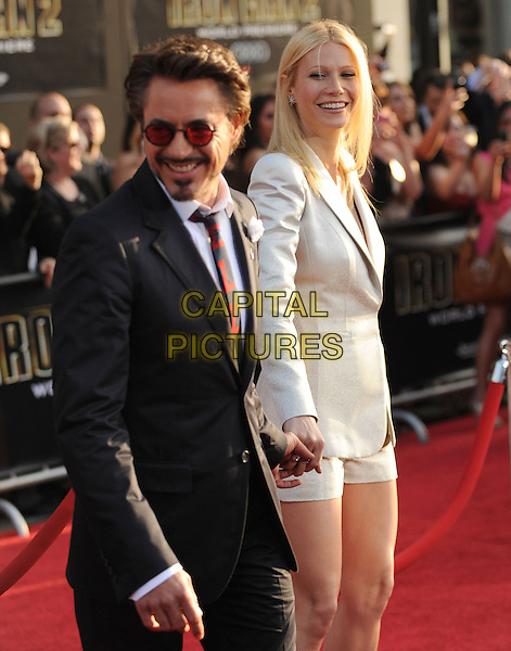 ROBERT DOWNEY JR. & GWYNETH PALTROW.The Marvel World Premiere of Iron Man 2 held at The El Capitan Theatre in Hollywood, California, USA..April 26th, 2010      .half length white Giorgio Armani degrade shorts shiny jacket blazer black clutch bag  shoulder pads shirt red striped tie suit tinted beard facial hair sunglasses shades holding hands  .CAP/RKE/DVS.©DVS/RockinExposures/Capital Pictures.