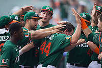 Michael Burns (44) of the Miami Hurricanes is mobbed by his teammates after scoring a run in the bottom of the first inning against the North Carolina Tar Heels in the second semifinal of the 2017 ACC Baseball Championship at Louisville Slugger Field on May 27, 2017 in Louisville, Kentucky.  The Tar Heels defeated the Hurricanes 12-4.  (Brian Westerholt/Four Seam Images)