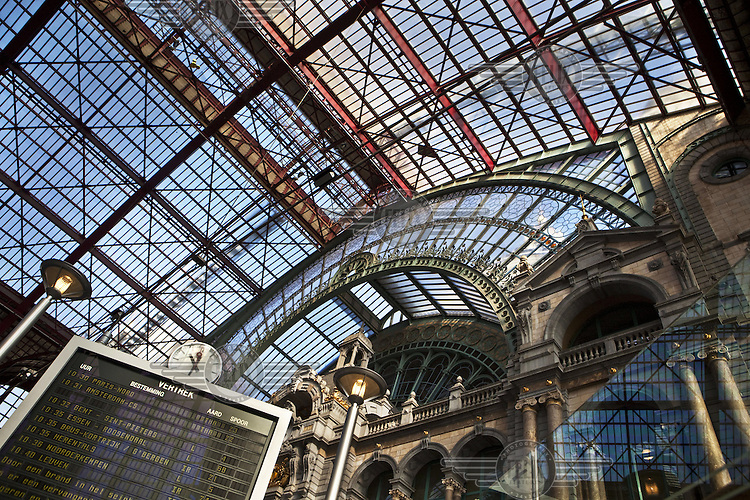 The departures board and impressive interior architecture of Antwerp Central train station.