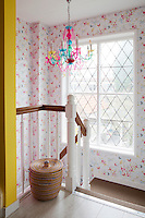 A large window floods the spacious stairwell with light, illuminating the colourful chandelier and floral wallpaper