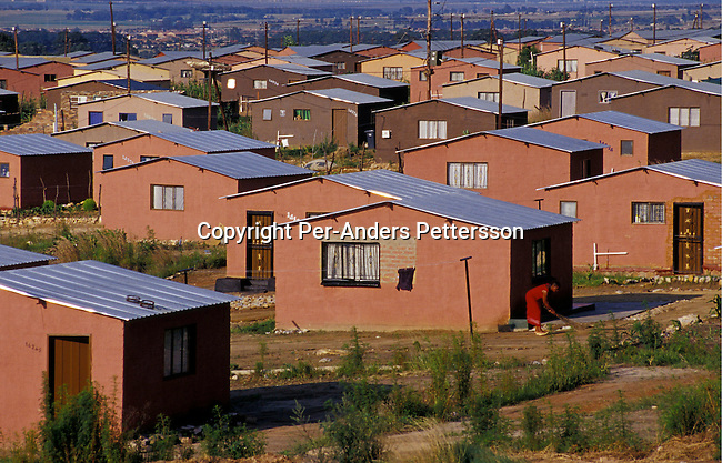dihoext00038. SOWETO, SOUTH AFRICA - FEBRUARY 15: An unidentified woman sweeps her garden outside her newly built RDP (rapid development program) government sponsored house, also known as Mandela houses, on February 15, 2004 in Soweto outside Johannesburg, South Africa. The government promised to build one million houses during the election in 1994 and about 1,7 million houses have been built. Still the housing backlog are estimated to about 6-7 million units, making it still a dream for many poor people in South Africa to own a house. .© Per-Anders Pettersson/iAfrika Photos....